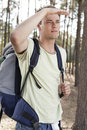 Young man with backpack shielding eyes in forest Royalty Free Stock Image
