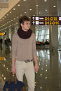 Young man with bag standing in airport hall Royalty Free Stock Photo