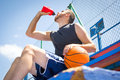 Young man with a basketball drinking water sitting Royalty Free Stock Photo
