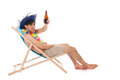 Young man at the beach drinking beer with tropical hat sitting in chair Royalty Free Stock Photo