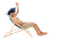 Young man at the beach with tropical hat sitting in chair Royalty Free Stock Image