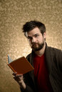 Young man with beard holding book portrait of reading over retro background Stock Photography