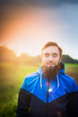 Young man with a beard in profile against green field and sky wearing blue jacket Royalty Free Stock Photography