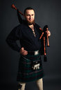Young man beard scottish costume pipe his hand studio shot Stock Image
