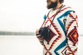 Young man bearded with retro photo camera fashion travel lifestyle wearing knitted sweater clothing outdoor foggy nature on Stock Image