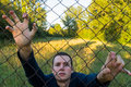 Young man behind a fence in nature and or wire mesh at sunset Stock Photography