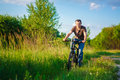 Young man on the bicycle in green summer sunny field Stock Photography