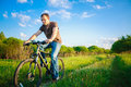 Young man on the bicycle in green summer sunny field Stock Images
