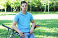 Young man with bicycle leaning on a in the park Royalty Free Stock Image
