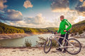 Young man with bike enjoy with beautiful mountain lake view Royalty Free Stock Photo