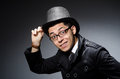 Young man in black coat and hat against gray Royalty Free Stock Photo