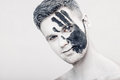Young man with black hand print on white face. Closeup Portrait. Professional Fashion Makeup. fantasy art makeup