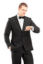 A young man in black suit with bow tie looking at wrist watch Royalty Free Stock Image