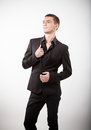 Young man in black suit standing against white background handsome Stock Photo