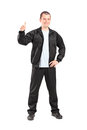 Young man in black tracksuit giving a thumb up full length portrait of isolated on white background Stock Image
