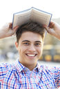 Young man with book over his head male student Stock Image