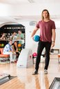 Young man with bowling ball in club men holding friends background at Royalty Free Stock Image