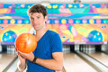 Young man bowling having fun in alley the sporty holding a ball in front of the ten pin alley Royalty Free Stock Photos