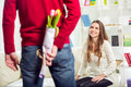 The young man brings flowers to his girlfriend men hes hiding behind their backs selective focus Royalty Free Stock Image
