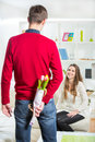 The young man brings flowers to his girlfriend men hes hiding behind their backs selective focus Stock Images