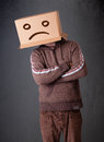 Young man with a brown cardboard box on his head with sad face standing Royalty Free Stock Image