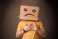 Young man with a brown cardboard box on his head with sad face standing Royalty Free Stock Photo