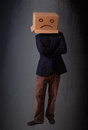 Young man with a brown cardboard box on his head with sad face standing Stock Photo