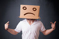 Young man with a brown cardboard box on his head with sad face standing Stock Photography