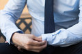Young man in business office shirt buttoning his sleeve buttons. Royalty Free Stock Photo