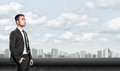 Young man in business suit, standing front of city landscape sunrise. Business, leadership and success concept Royalty Free Stock Photo