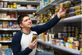 Young man buying tinned food positive smiling at grocery store Stock Photo