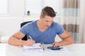 Young man calculating invoice with calculator at desk Stock Image