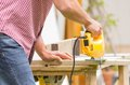 Young man carpenter working with electric jigsaw Royalty Free Stock Photo