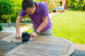 Young man - carpenter working with electric sander in the garden Royalty Free Stock Photo