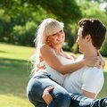 Young man carrying girlfriend in arms. Stock Photography