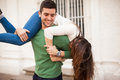 Young man carrying his girlfriend portrait of a handsome men having fun with and her Stock Images