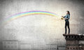 Young man in casual splashing rainbow from bucket Royalty Free Stock Photo