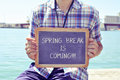 Young man with a chalkboard with the text spring break is coming caucasian sitting in wooden pier shows written in it filter Stock Images