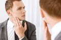 Young man checking his bristle hair on face intent glance handsome looking in mirror and Royalty Free Stock Photos