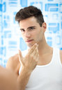 Young man checks his beard looking at mirror Royalty Free Stock Image