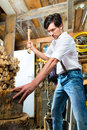 Young man chopping fire wood in mountain chalet chops firewood or with a hatchet or an axe a shack the mountains Stock Images