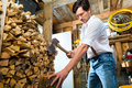 Young man chopping fire wood in mountain chalet chops firewood or with a hatchet or an axe a shack the mountains Royalty Free Stock Images