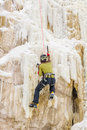 Young man climbing the ice using axe Royalty Free Stock Images
