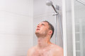 Young man with closed eyes taking a shower in the bathroom Royalty Free Stock Photo