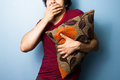 Young man clutching cushion while watching scary movie a Royalty Free Stock Image