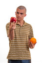 Young man comparing apple to orange apples oranges Royalty Free Stock Image