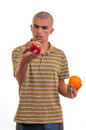 Young man comparing apple to orange apples oranges Royalty Free Stock Photography