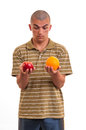 Young man comparing an apple to an orange studio shot of a Stock Photography