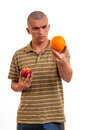 Young man comparing orange to apple red Stock Photo