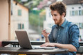 Young man connecting with a laptop at the bar and drinking cappuccino town buildings on background Royalty Free Stock Image
